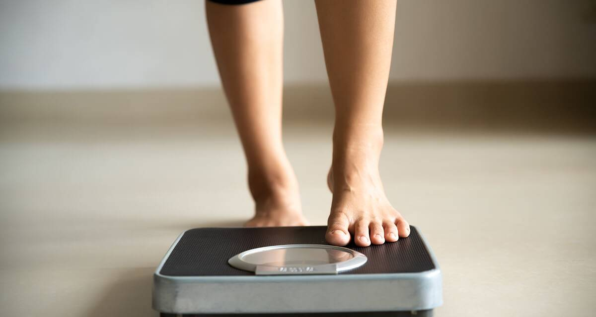 a woman steps on a scale. REWIRE PBS Work weight loss workplace wellness