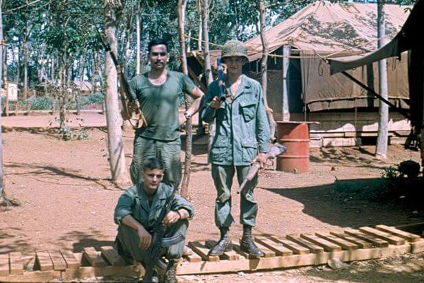 Three soldiers standing with their rifles outside a camp.