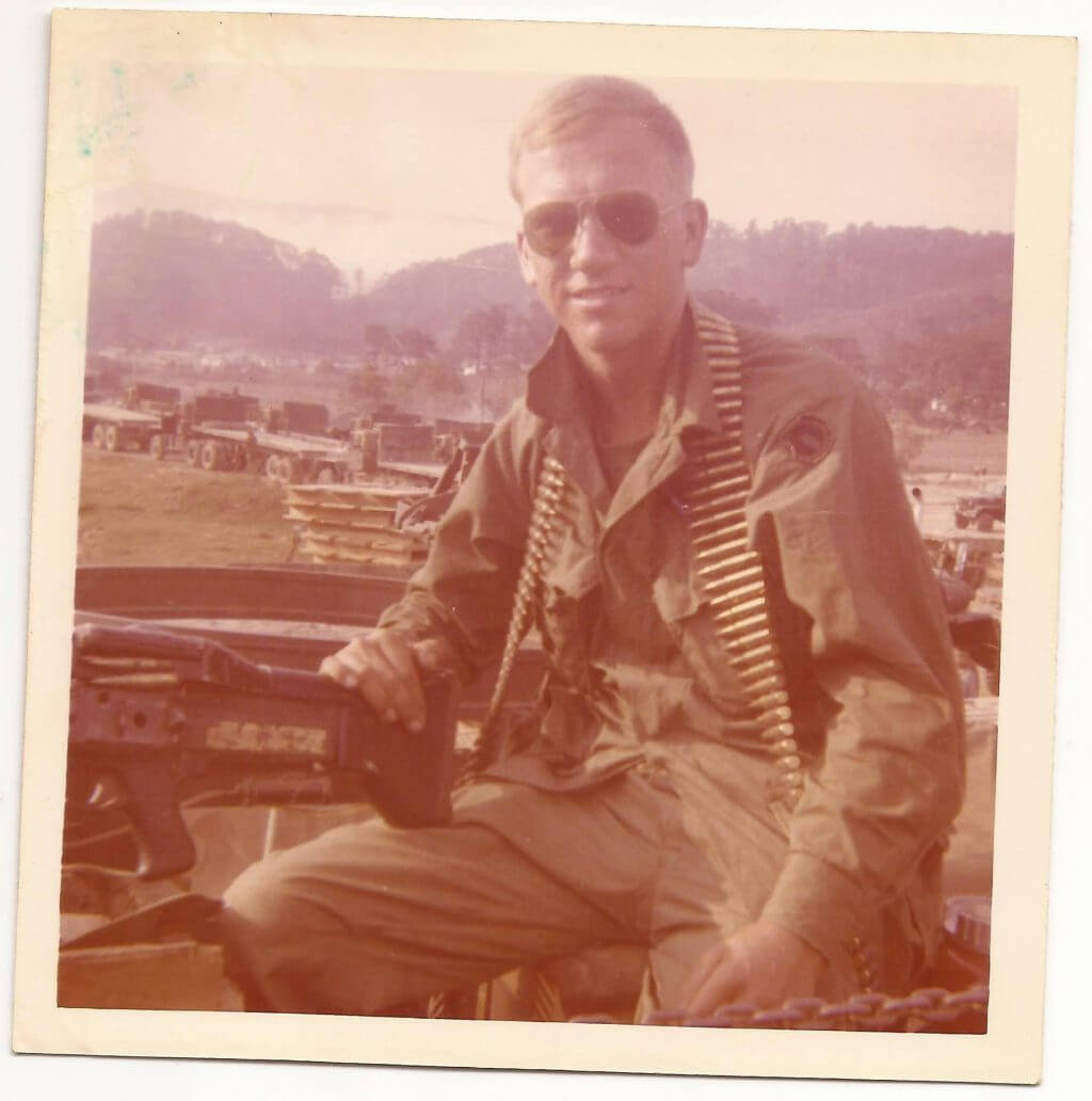 Young soldier sitting on a truck with aviator sunglasses on and a bandolier around his neck.