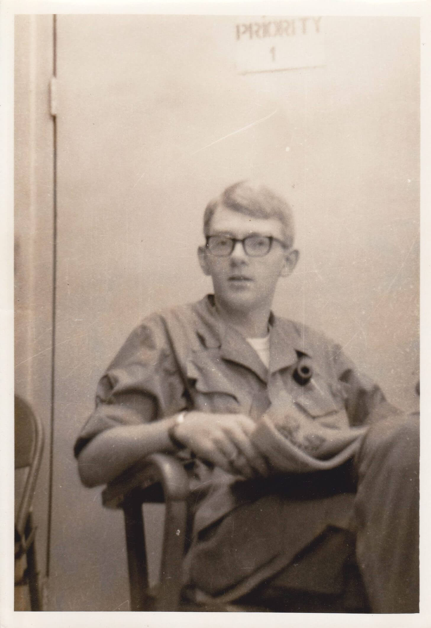 Young soldier with glasses, sitting and reading a newspaper.