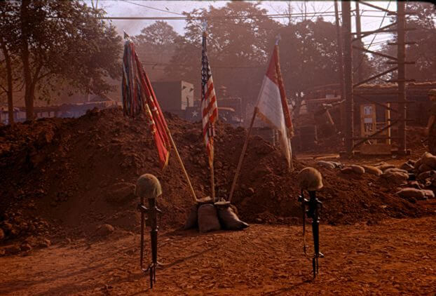 Rifles planted in the ground with helmets on top, flags in the background.