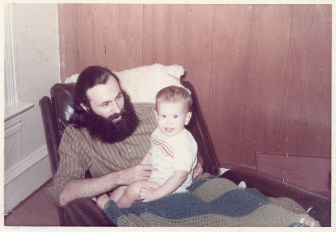 Infant sitting on father's lap.