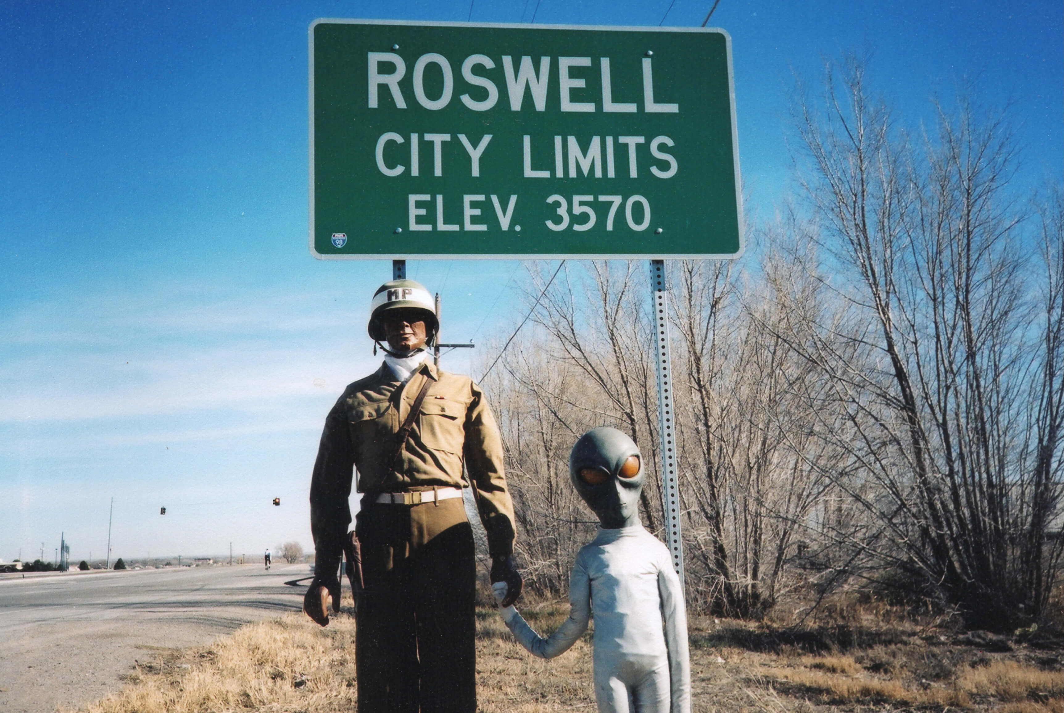 "A mannequin in uniform holding the hand of a squat alien figure, in front of a sign that reads ""Roswell City Limits, Elev. 3570."""