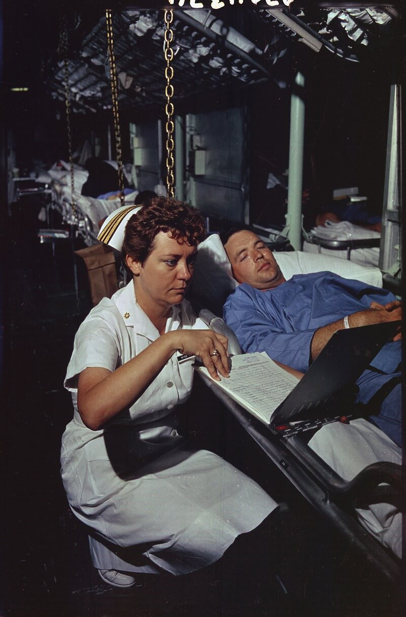 Nurse in naval uniform checking in on a patient.