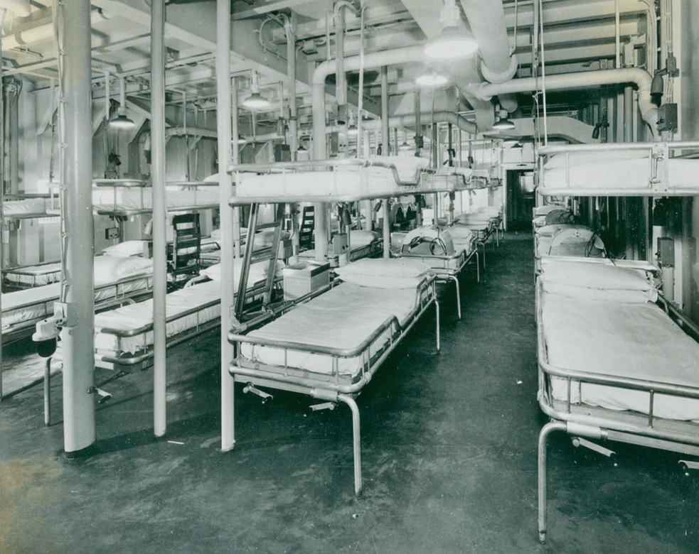 Interior of a medical ward on a ship, bunks two high.