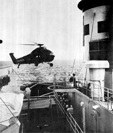 A chopper approaching the landing pad of a large ship.