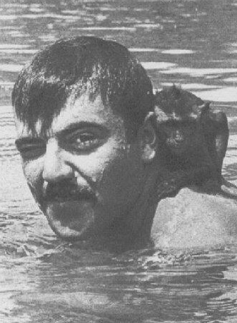 Close up on a U.S. soldier swimming in a body of water, small monkey hanging onto his neck.