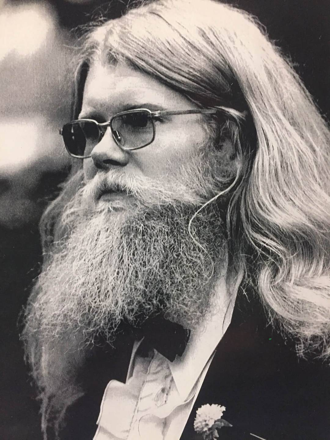 A man with long hair, a beard, and tinted glasses in a suit and bow tie with a carnation boutonniere.