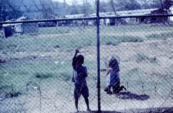 Small Asian children standing on the other side of a chainlink fence.