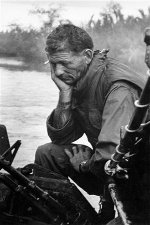 An older U.S. soldier looking sad and reflective, sitting on a boat.