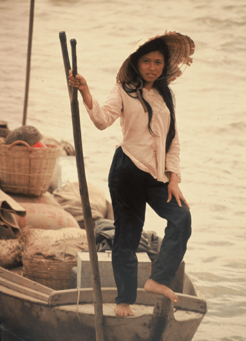 Young Vietnamese woman with a straw hat, standing on a fishing boat.