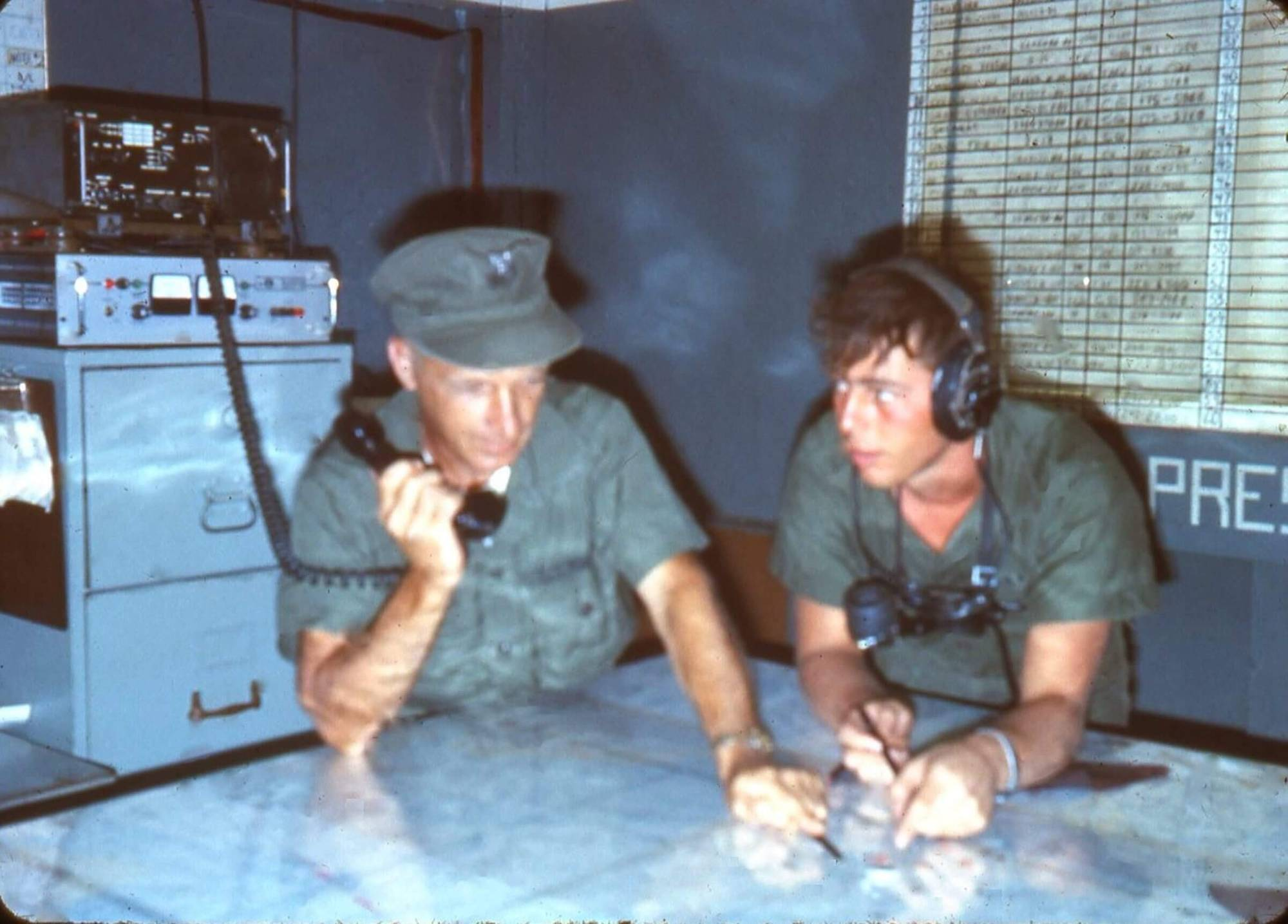 Two soldiers, one young and one old, leaning over table and talking into a phone.
