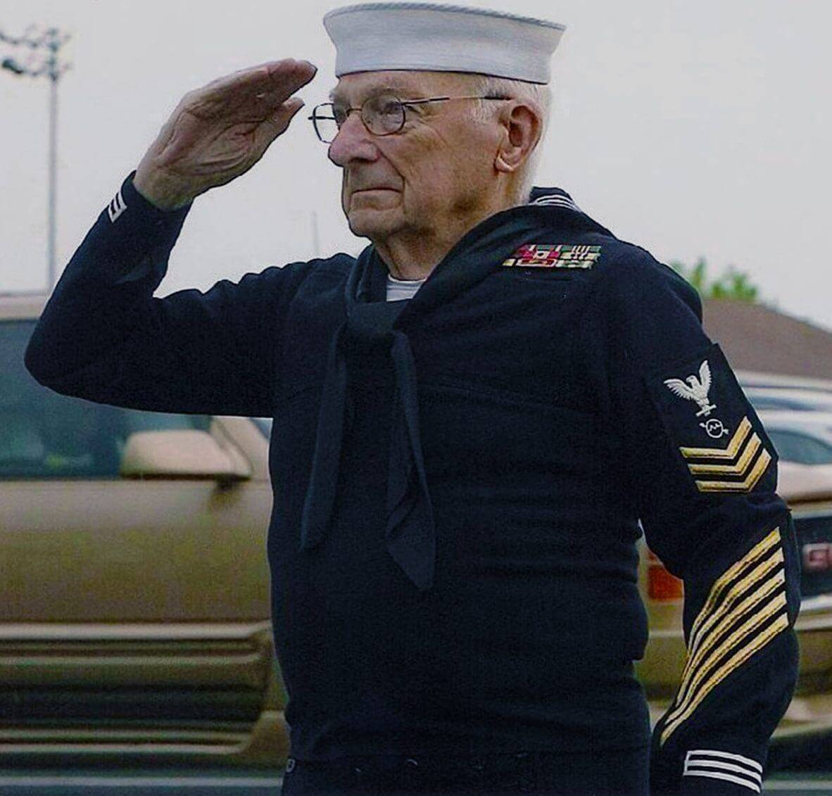 Elderly vet in naval uniform, saluting.