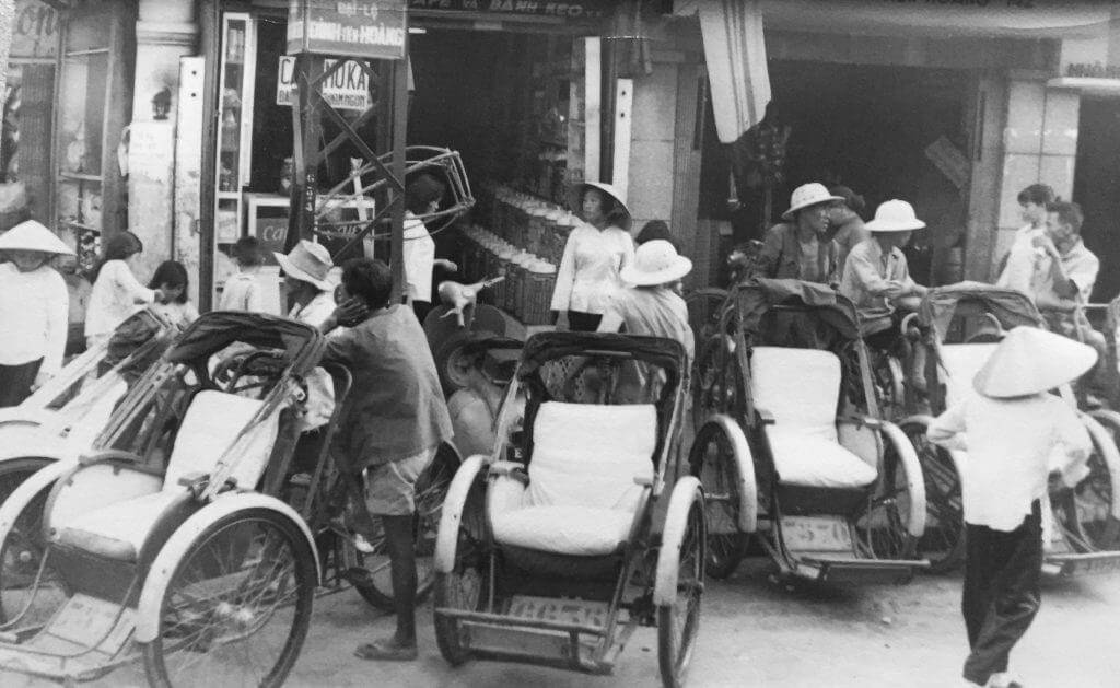 Black and white photo of empty pedicabs on a street.
