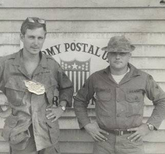 Two young men in uniform, posed with their hands on their hips.