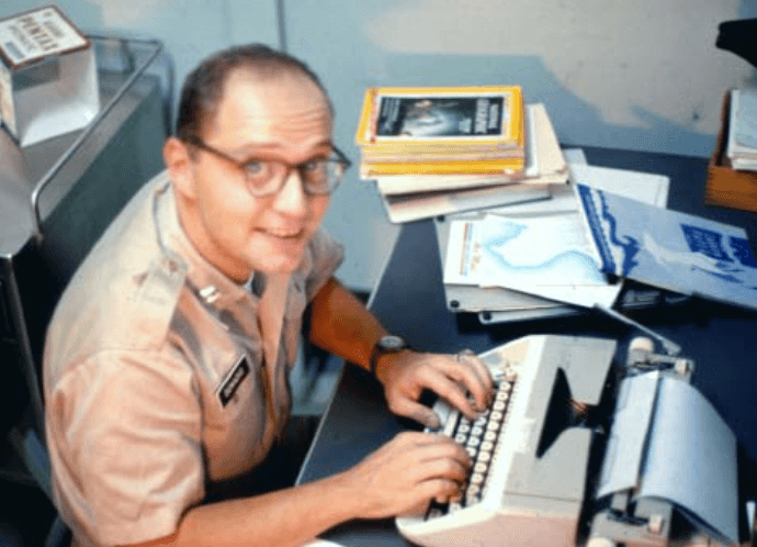 Dr. Donadio at desk, typing on typewriter and looking at the camera