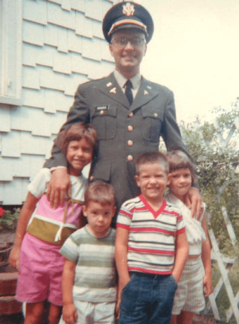 Dr. Donadio in uniform posing outside with his four young children