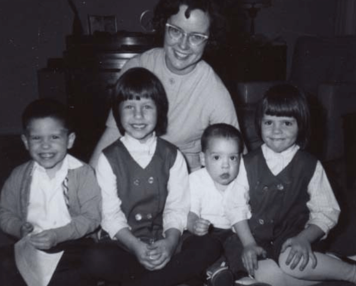 Black and white photo of four young children and mother
