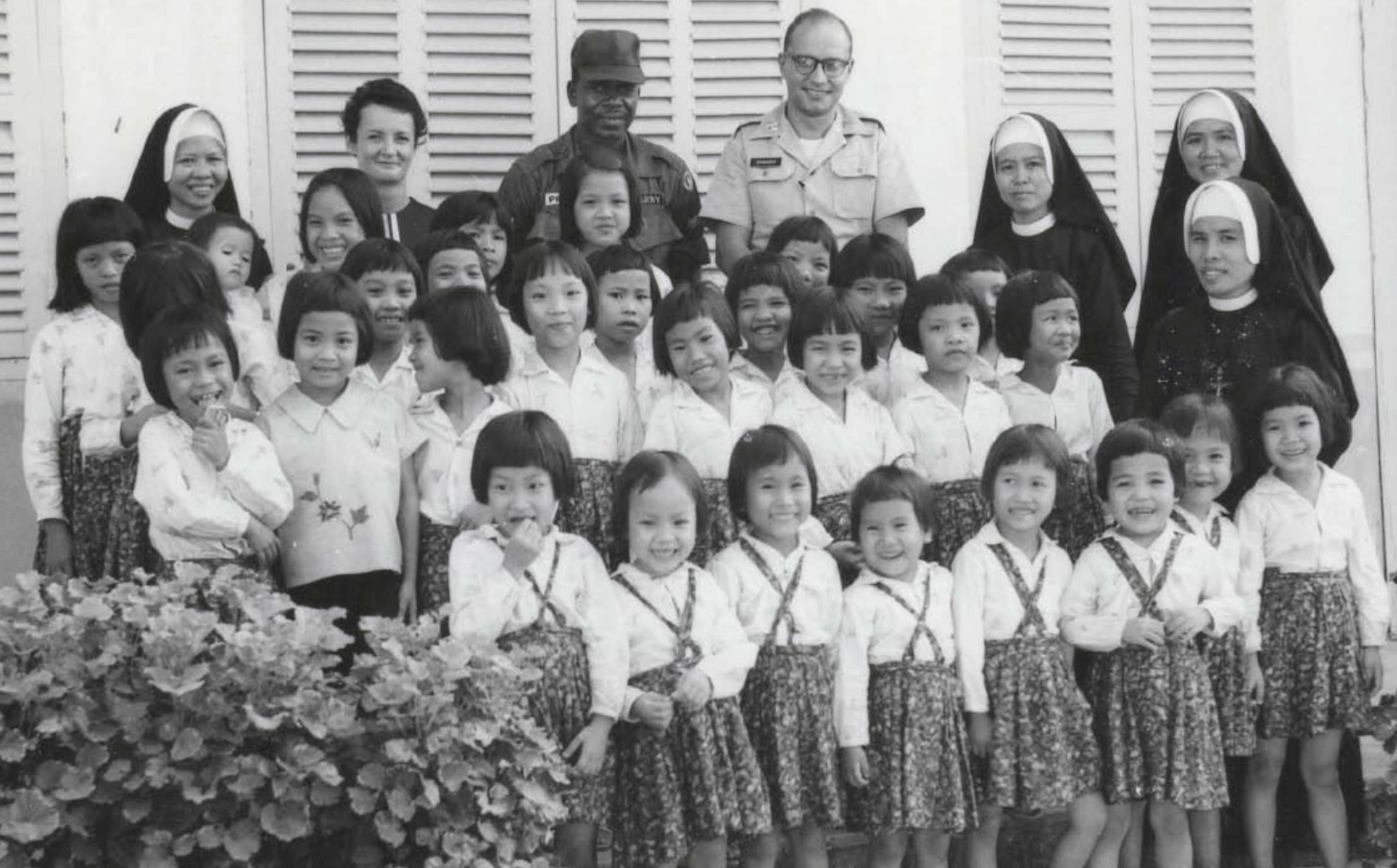 Dr. Donadio and one other serviceman with nuns and young orphaned girls.