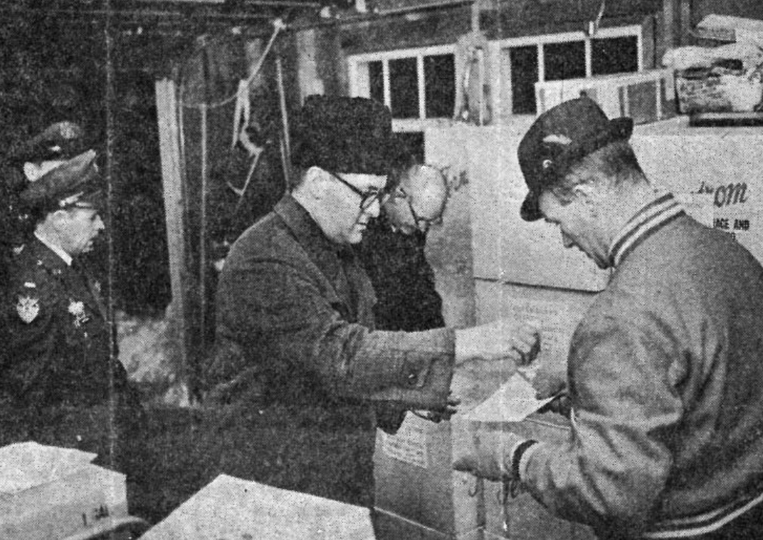 Black and white photo from newspaper, servicemen with packed boxes.