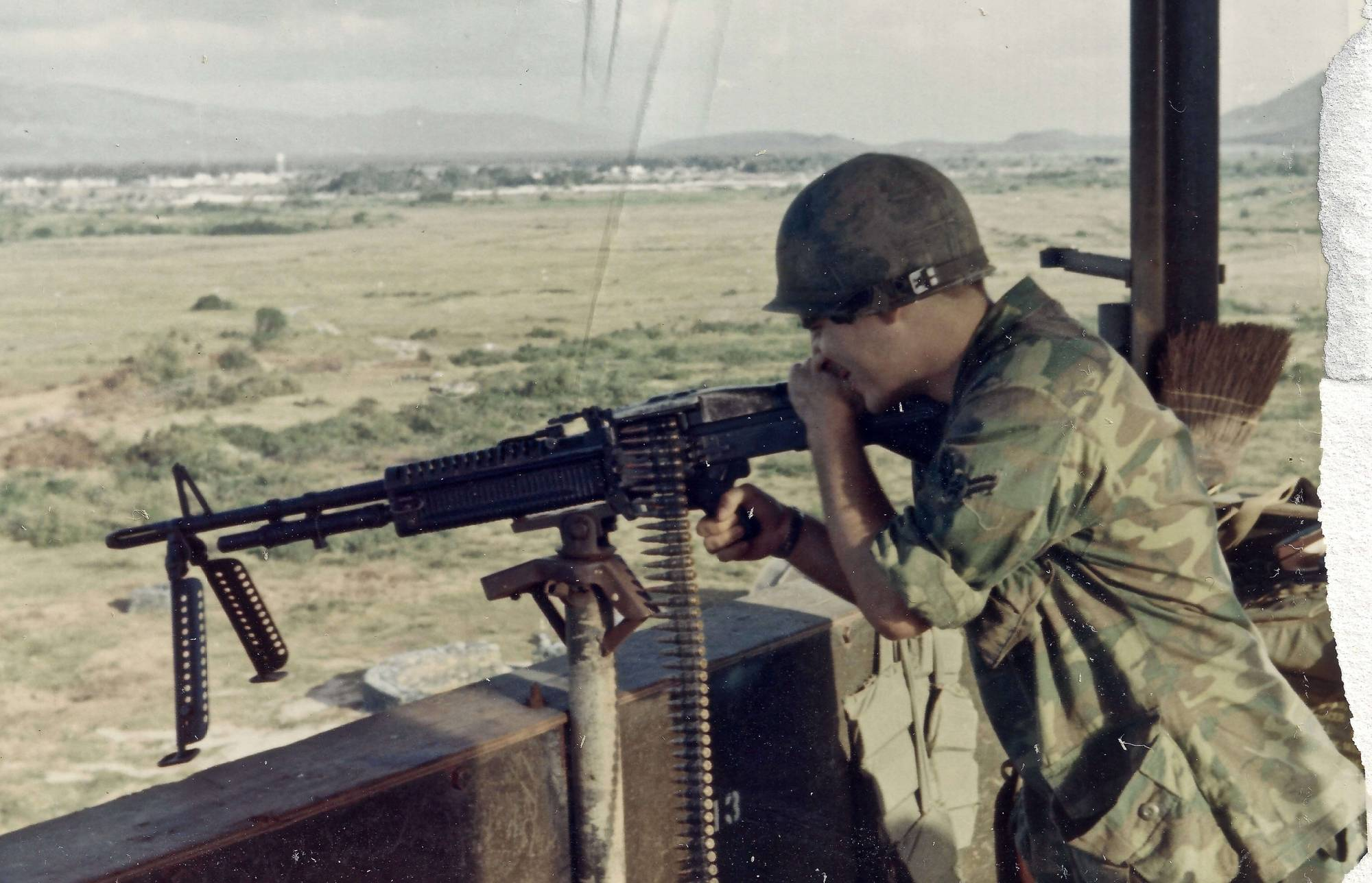 Young soldier in a watch tower, shooting an M-60 rifle.