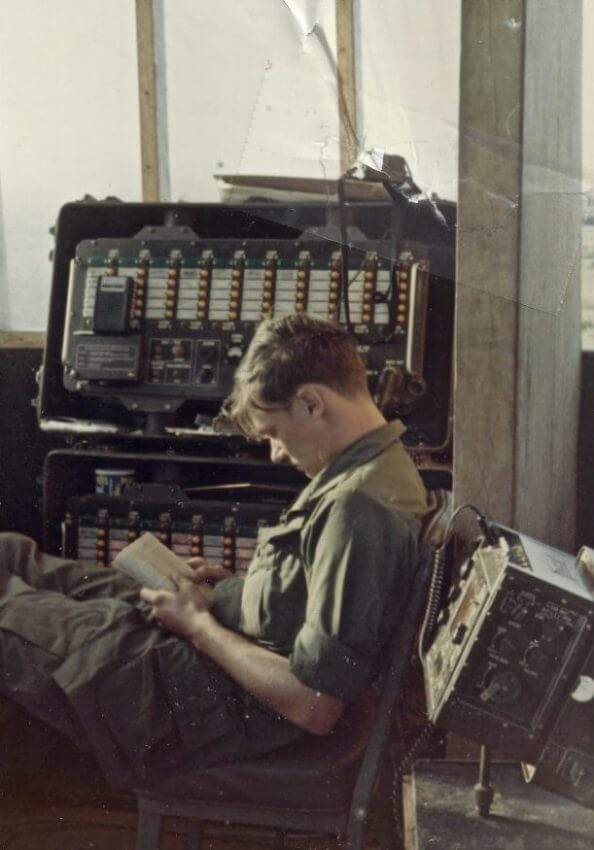 Young U.S. soldier relaxing and reading a book amid a bunch of technology.
