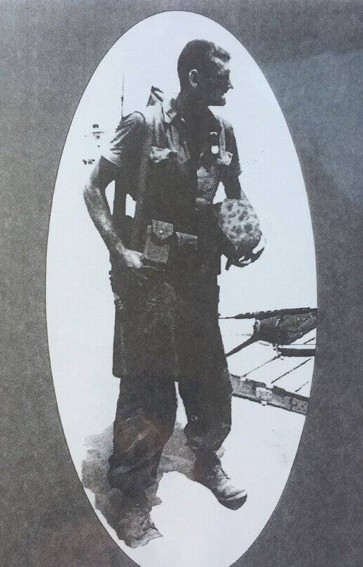 A grainy photo of a young man in full combat gear.