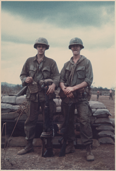 Two young soldiers in full gear, helmets; standing in front of a row of sandbags.