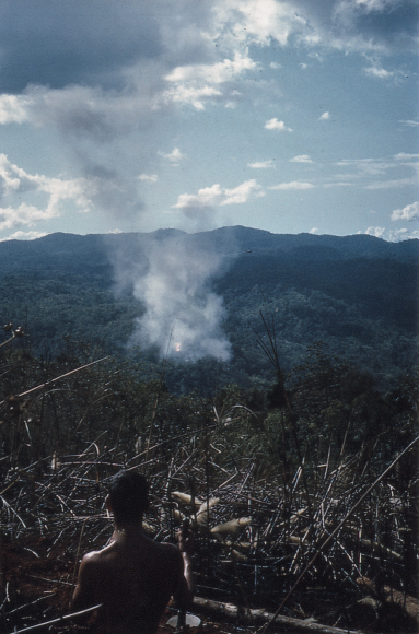 A young shirtless soldier on a mountain peak, looking over a smokey valley.
