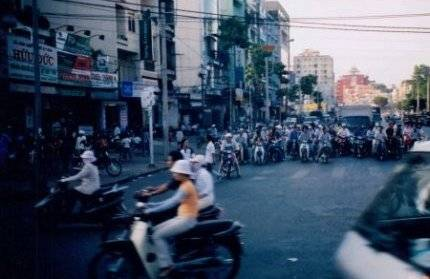 A city street with lots of Vietnamese people on motorbikes.