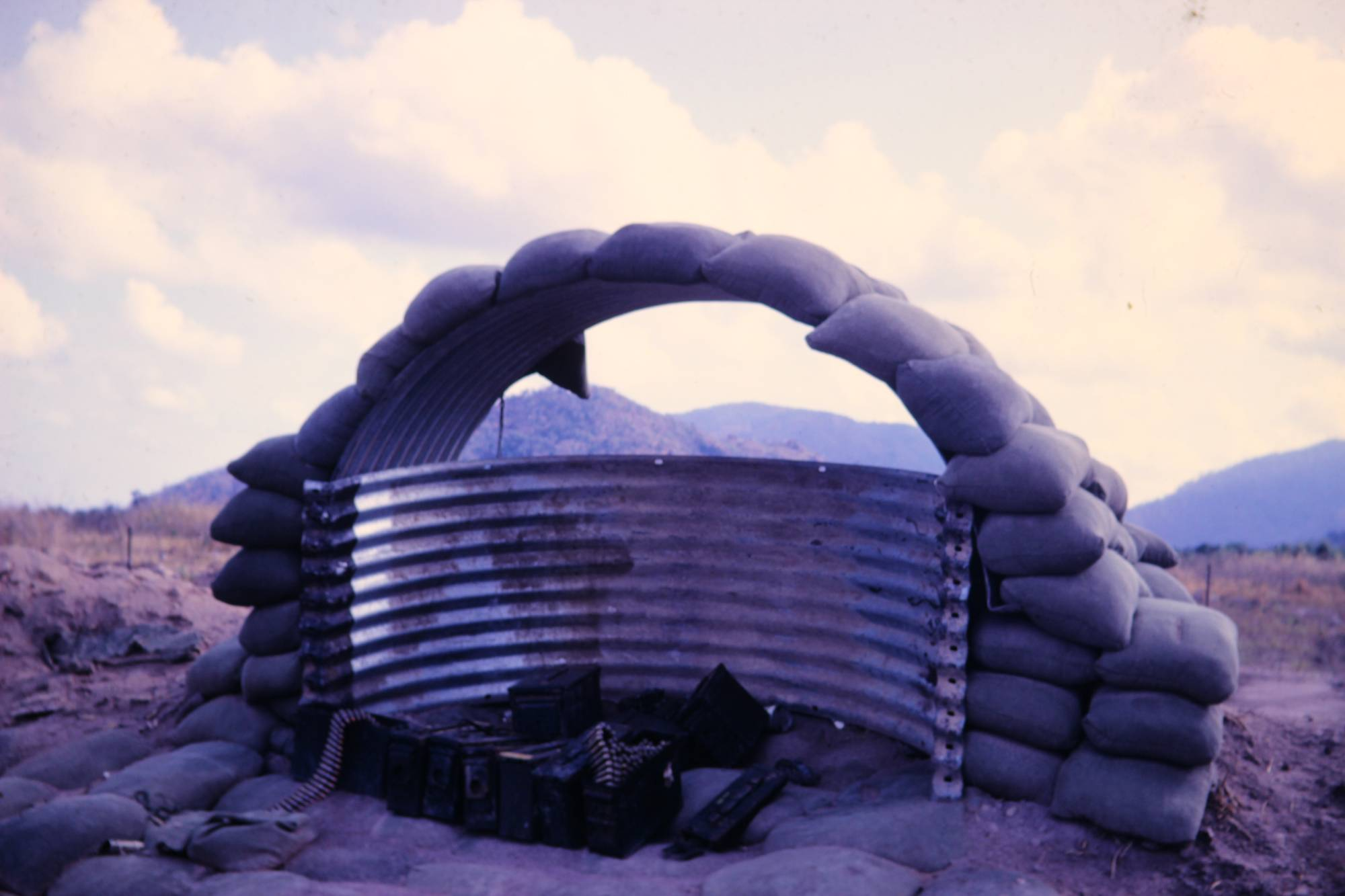A guard station on top of a hill, made from corrugated metal and sandbags.
