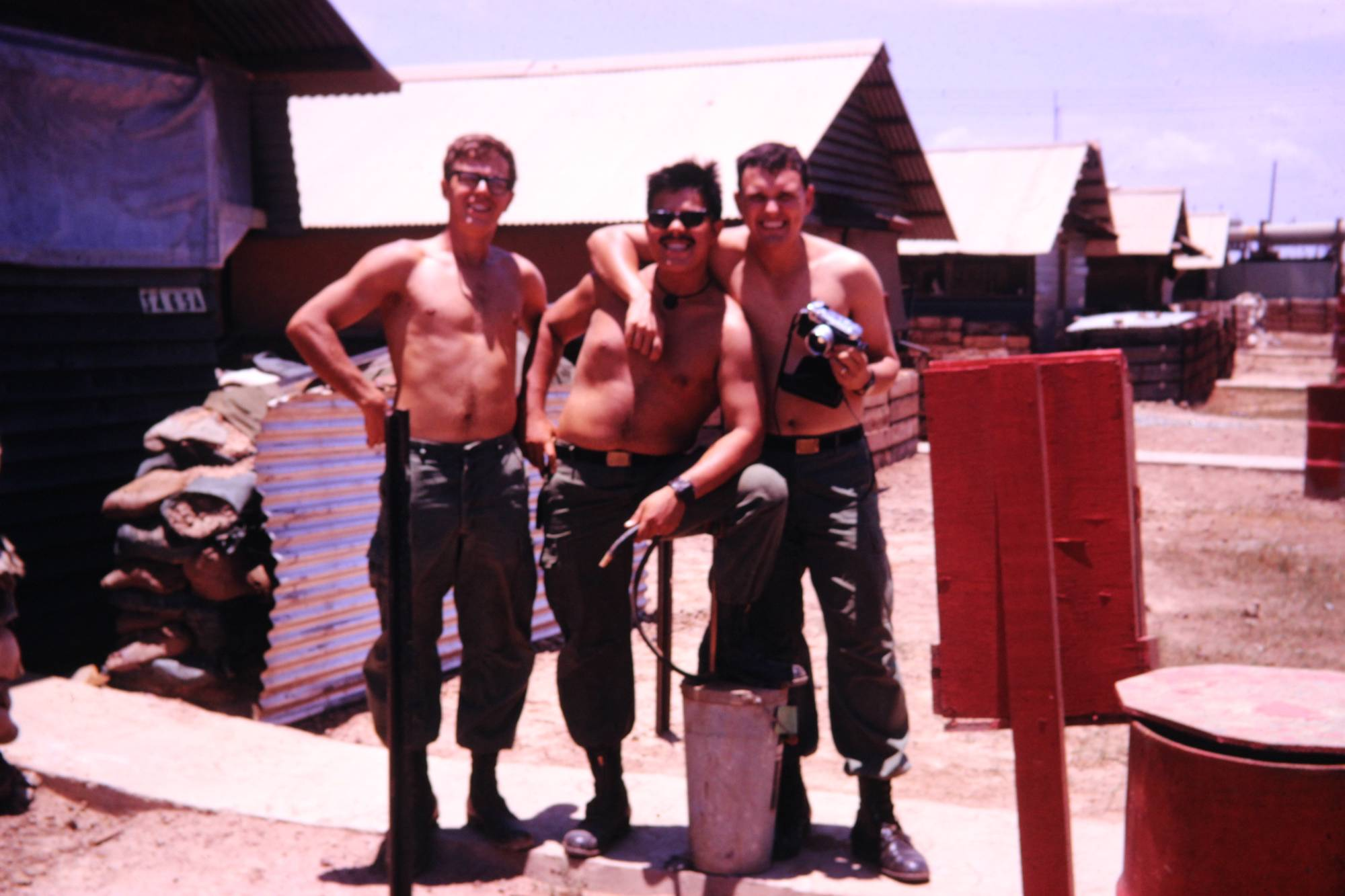 Three shirtless soldiers outside temporary living quarters.