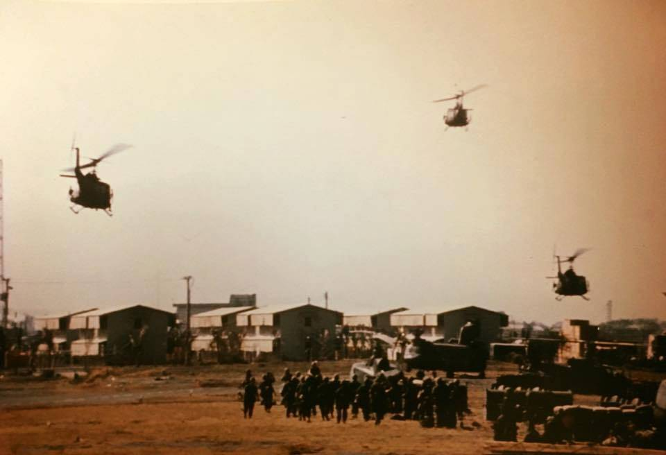 Three helicopters in the sky above a basecamp, soldiers on foot below.