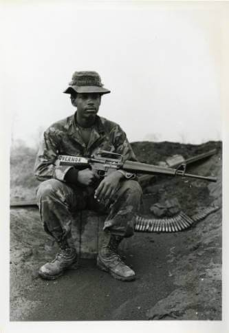 A young U.S. soldier sitting, gun rested across his lap.
