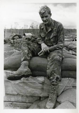 A young U.S. soldier sitting on sandbags.