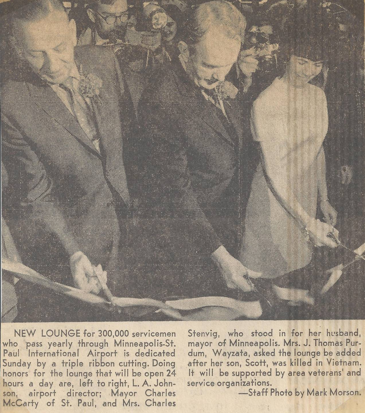 A news clipping that features three people wielding scissors, cutting a ribbon.