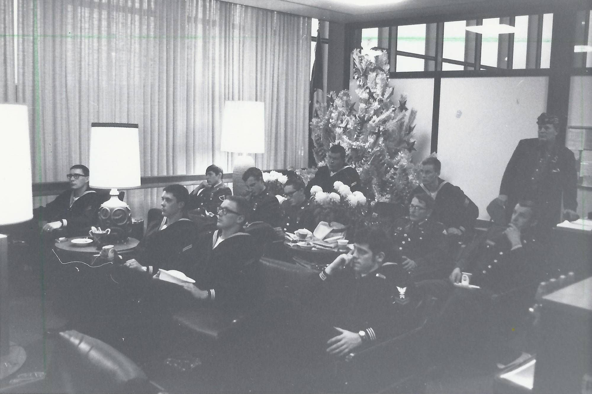 Servicemen sitting on leather seats in a lounge, Christmas tree in the background.
