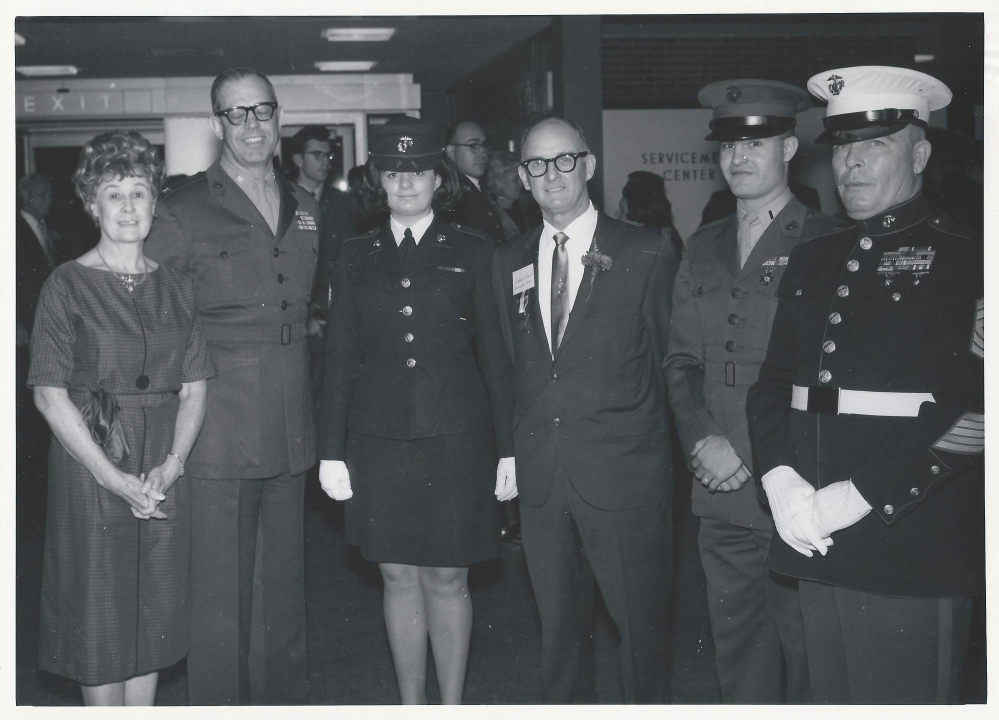 Servicemen and servicewoman and a civilian woman pose for a photo.