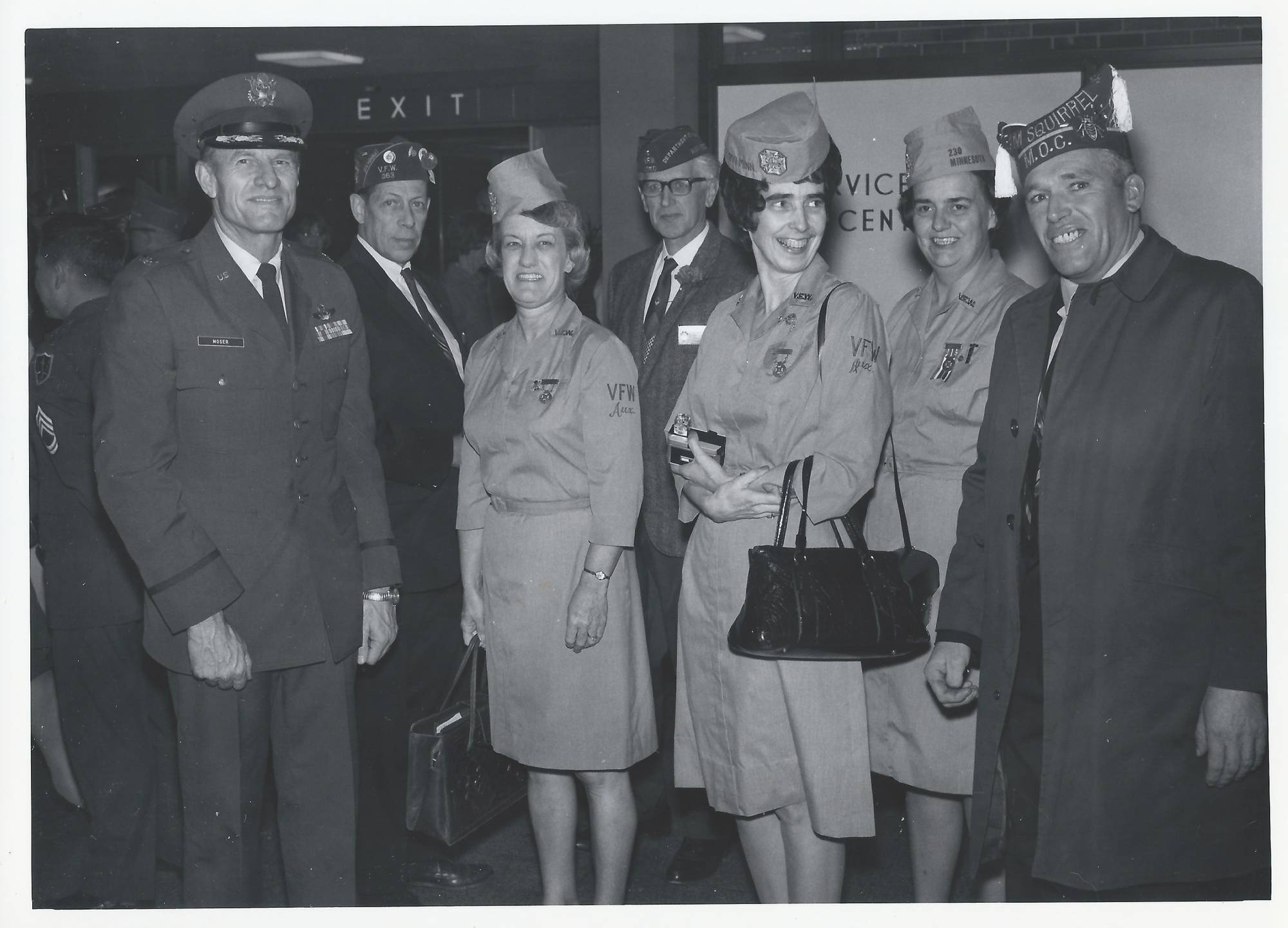 Older servicemen and servicewomen smiling for the camera.