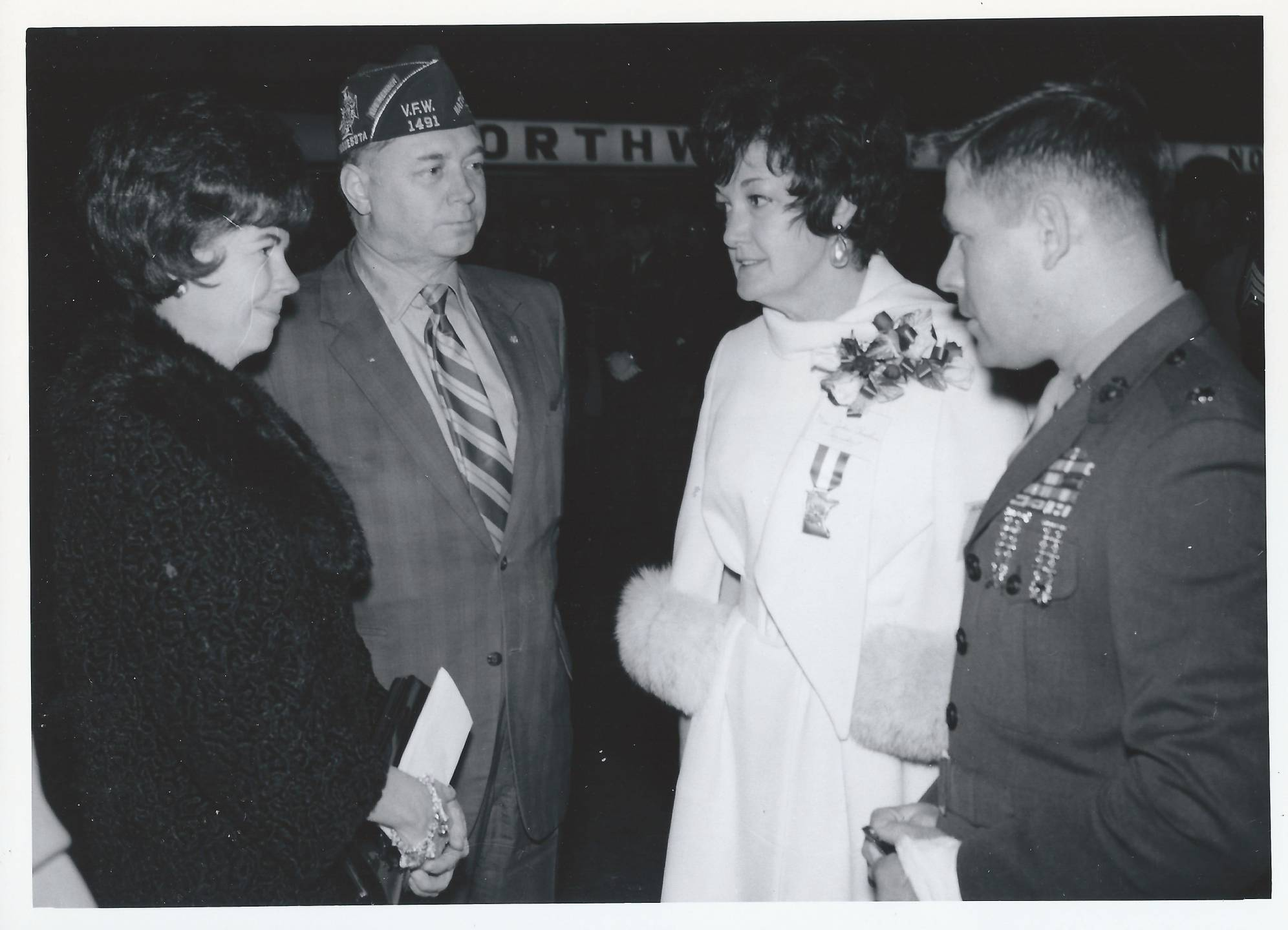Two servicemen and two women conversing.