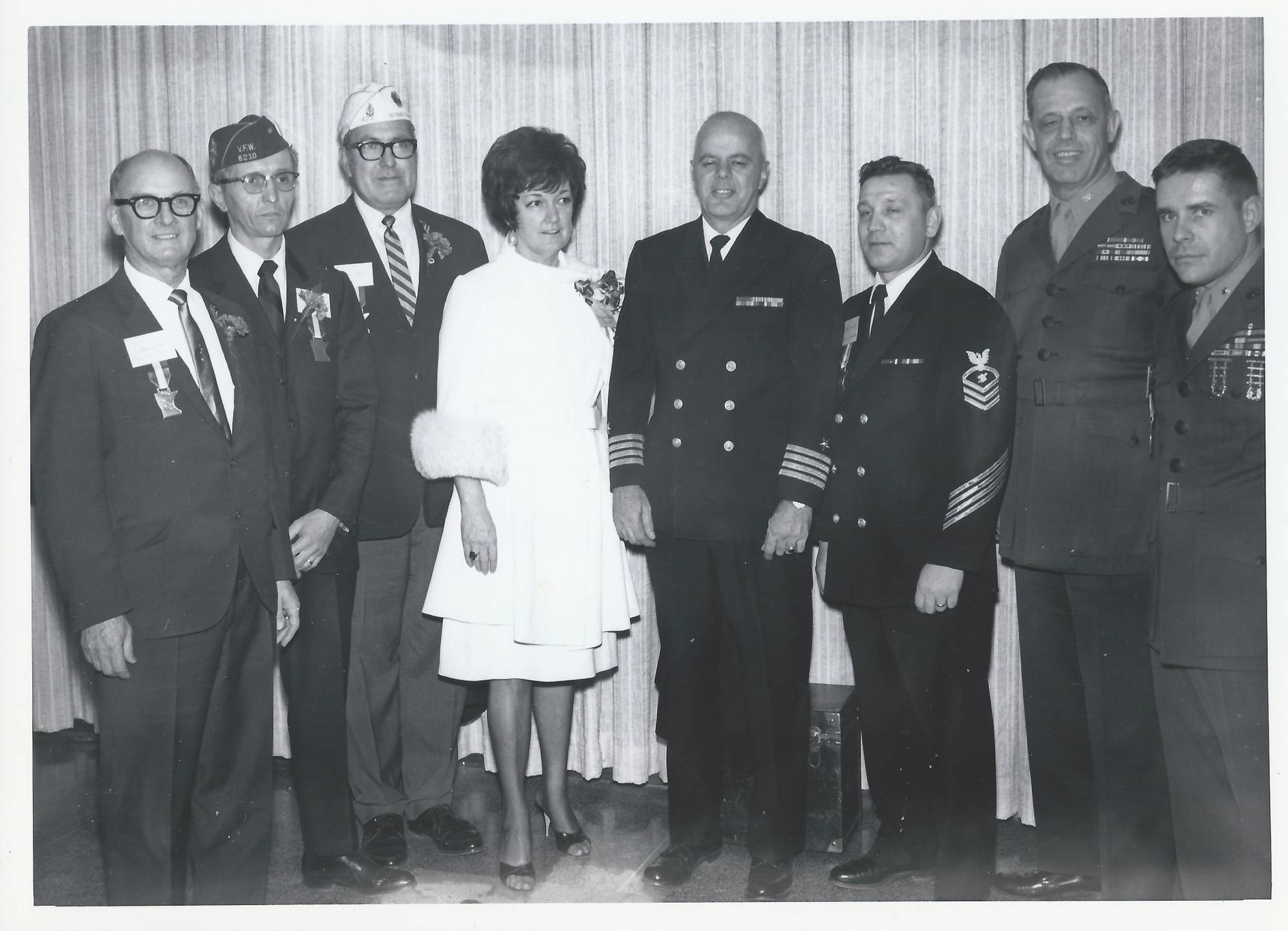 Posed photo of several servicemen, one civilian man, and one civilian woman.