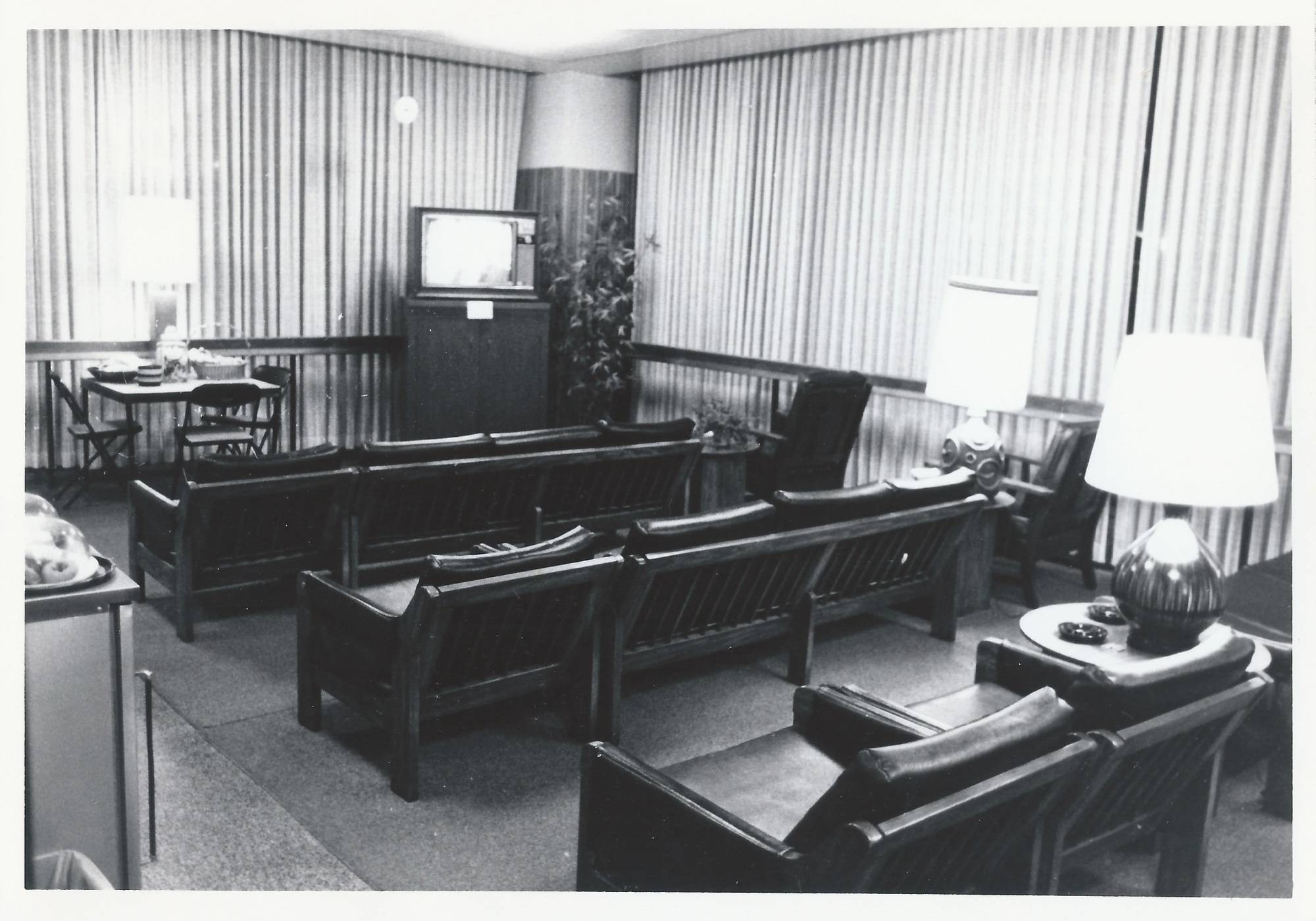 An empty lounge, vertical slat blinds, leather chairs, lamps, plants and a television set.