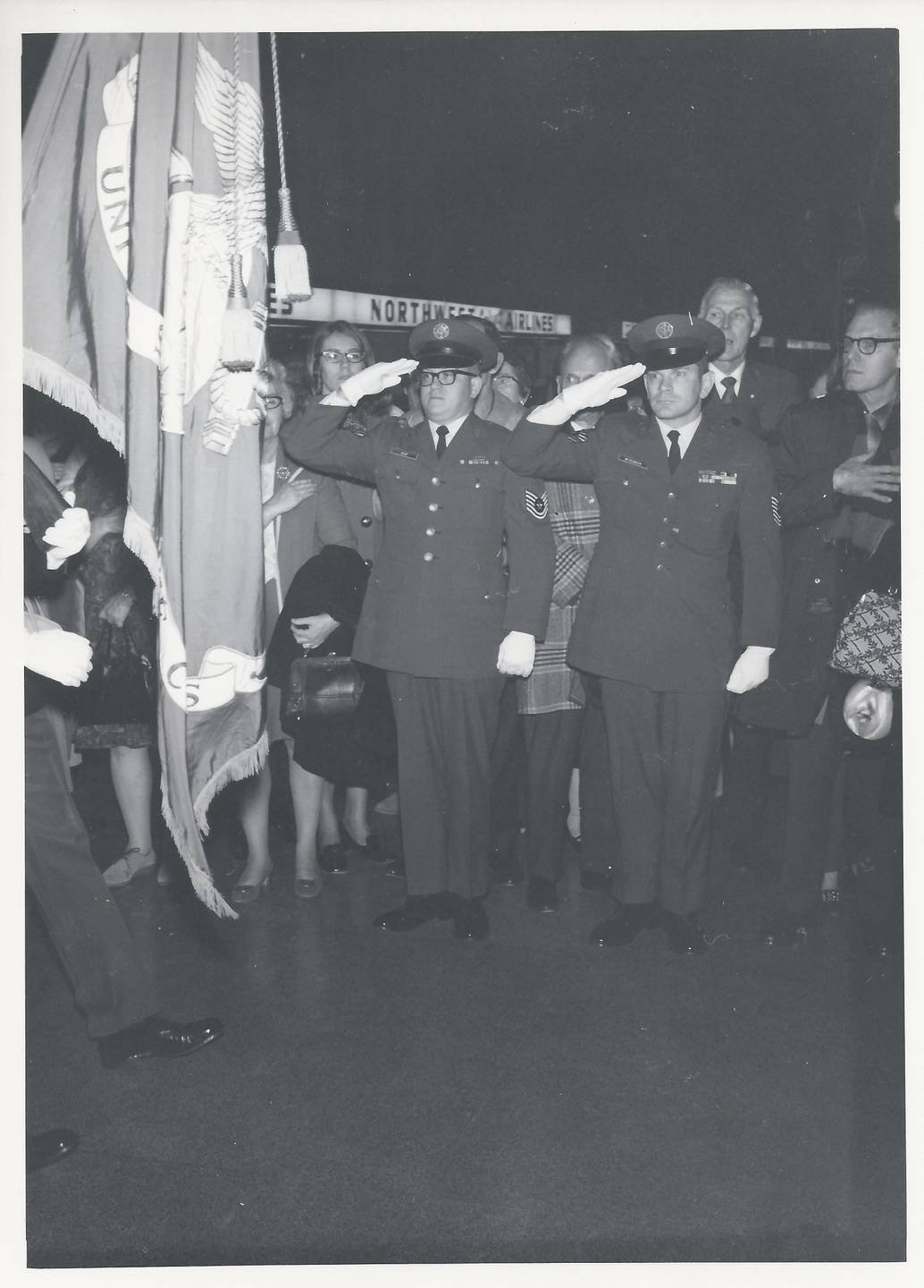 Two men in uniform saluting the flag while others watch.