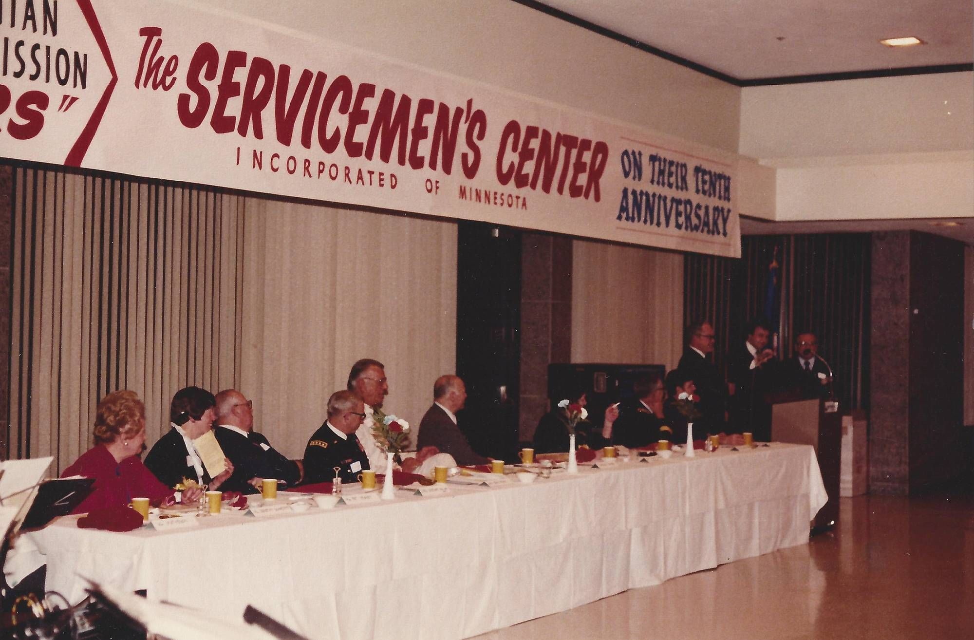 People seated at a long table with a white table cloth, looking towards a podium with a man speaking.