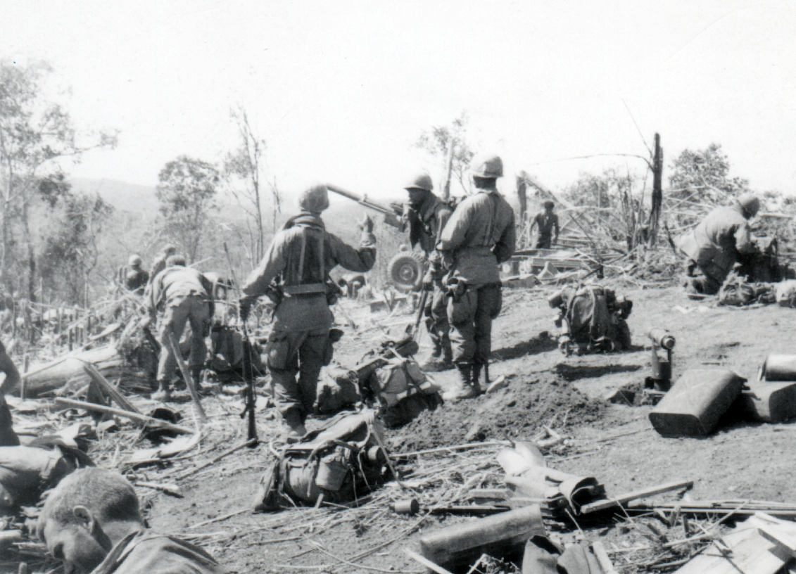 A hillside littered with gear and men, setting up.