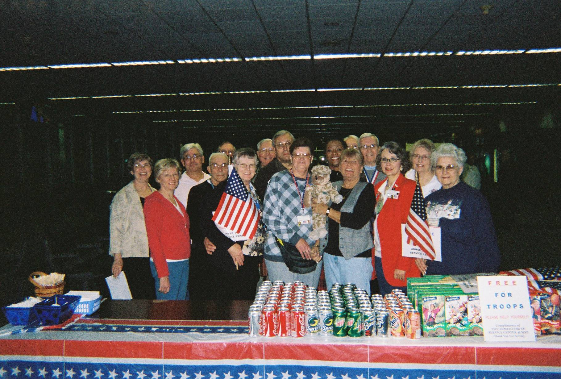 Contemporary photo of a group of people with miniature American flags, standing behind a table of refreshments.