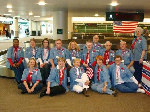 Contemporary photo of a group of people wearing red, white, and blue, seated near a luggage carousel.