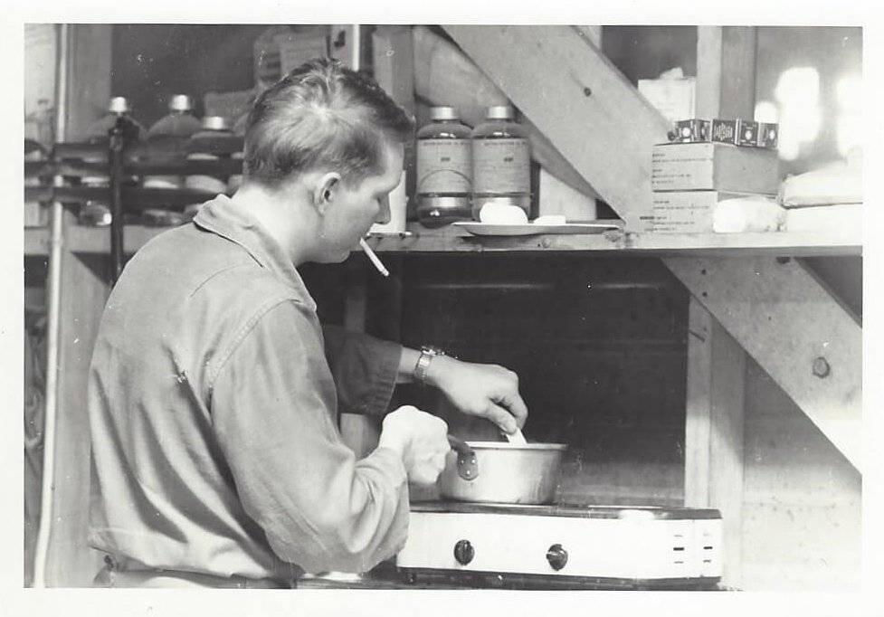 A young man cooking over a stove, cigarette in mouth.