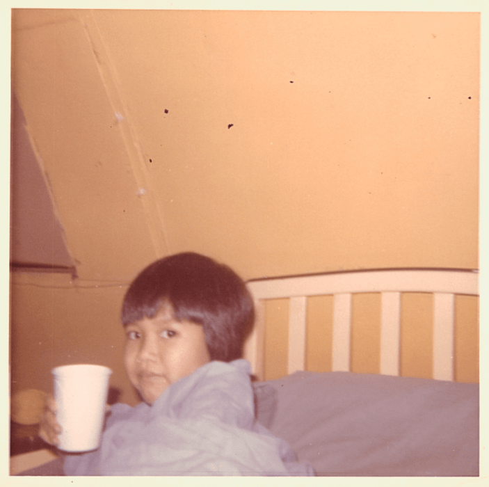 Young Asian patient wrapped in a blanket, drinking from a paper cup.