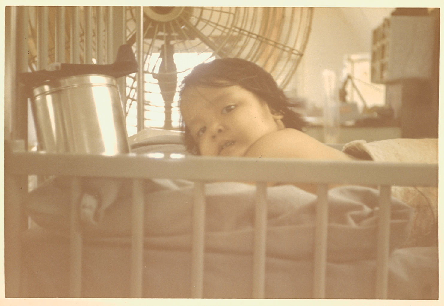 A young Asian child in her hospital bed.